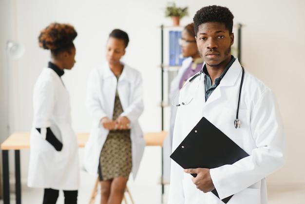 Joven médico africano sonriendo mientras está de pie en un pasillo del hospital con un grupo diverso de personal en el fondo