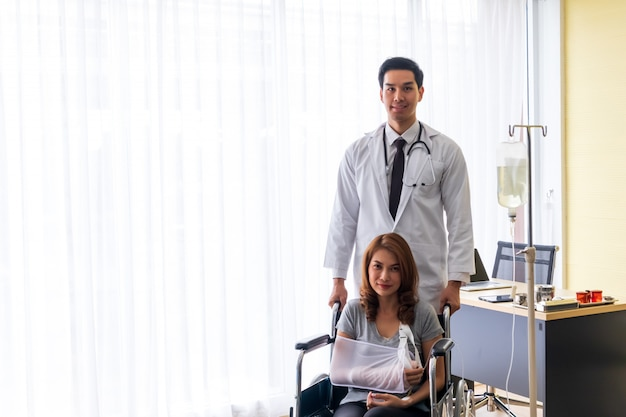 El joven médico alentó a la paciente en el brazo roto y la paciente en silla de ruedas.