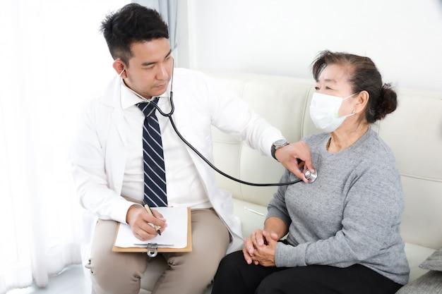 Joven médico asiático hablando con una mujer mayor en el hospital