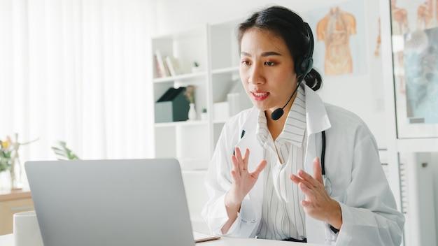 Joven médico asiático en uniforme médico blanco con estetoscopio usando computadora portátil