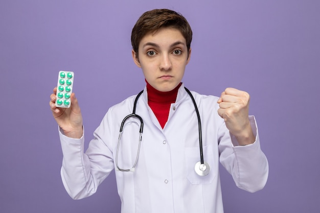 Joven médico en bata blanca con estetoscopio alrededor del cuello sosteniendo blister con pastillas con cara seria mostrando puño parado sobre pared púrpura
