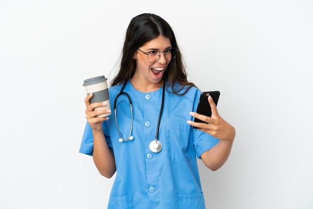 Joven médico cirujano mujer caucásica aislada sobre fondo blanco sosteniendo café para llevar y un móvil