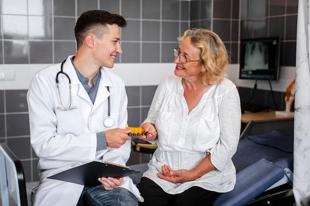 Joven médico dando pastillas a paciente femenino