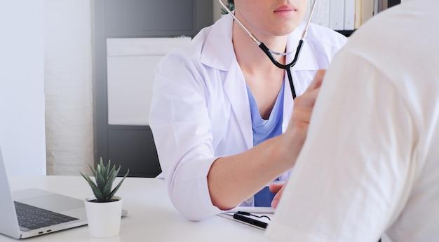 Joven médico diagnóstico paciente en la clínica.