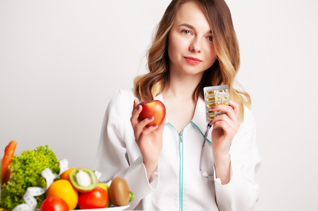 Joven médico dietista en consultorio en mesa con frutas y verduras frescas