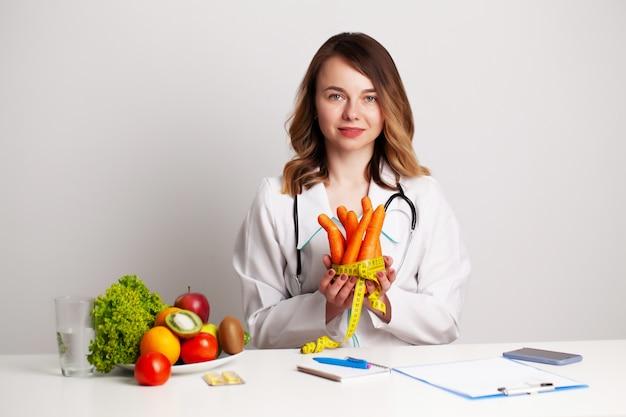 Joven médico dietista en la sala de consulta en la mesa con frutas y verduras frescas, trabajando en un plan de dieta