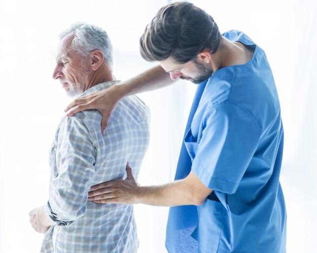 Joven médico examinar la parte posterior del paciente