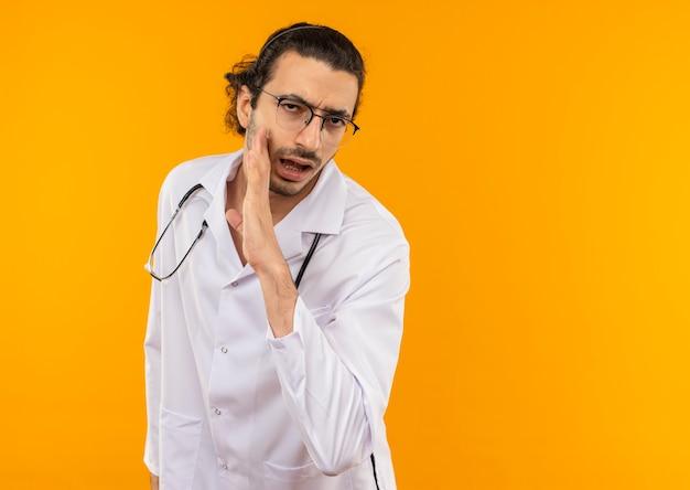 Joven médico con gafas médicas vistiendo bata médica con estetoscopio susurra