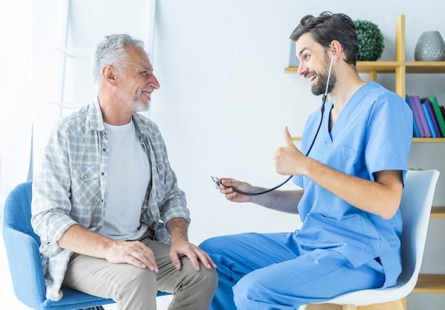 Joven médico gesticular pulgar arriba al paciente anciano