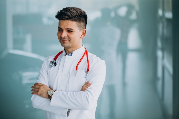 Joven médico guapo en una túnica médica con estetoscopio