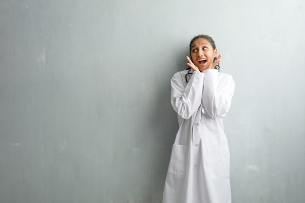 Joven médico india contra una pared sorprendida y conmocionada, mirando con los ojos bien abiertos, emocionada por una oferta o por un nuevo trabajo, gana el concepto