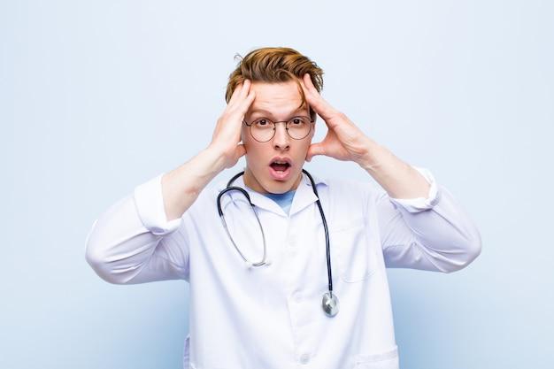 Joven médico jefe rojo levantando las manos a la cabeza