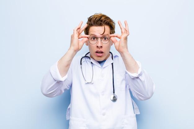 Joven médico jefe rojo sintiéndose sorprendido, asombrado y sorprendido, sosteniendo gafas con una mirada asombrada e incrédula contra la pared azul