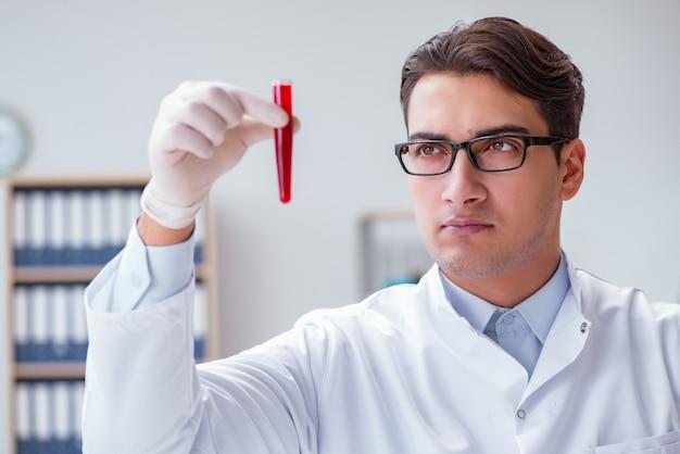 Joven médico en el laboratorio con tubo rojo