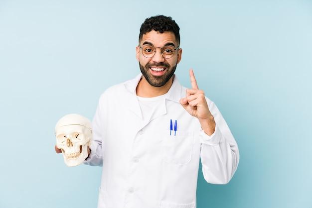 Joven médico latino sosteniendo una calavera con una idea, concepto de inspiración.