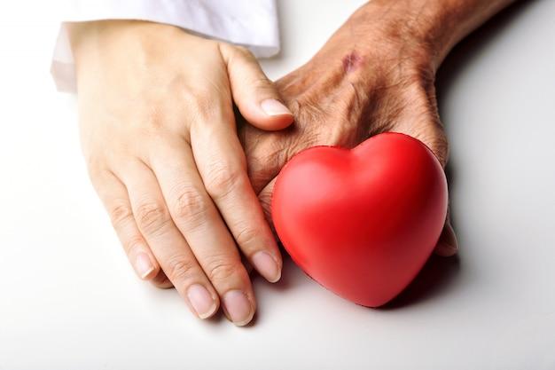 Joven médico de la mano del paciente senior para ayudar y apoyar con corazón rojo
