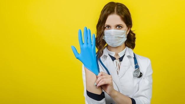 Joven médico con una máscara médica desechable se pone guantes quirúrgicos estériles en su brazo aislado sobre un fondo amarillo, protección contra el coronovirus. bandera