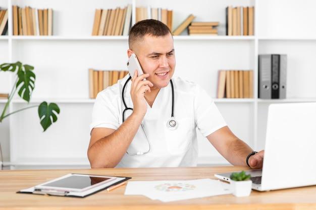 Joven médico masculino hablando por teléfono