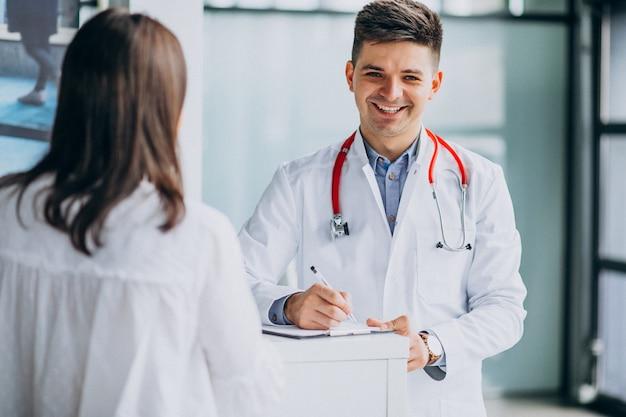 Joven médico masculino con paciente en el hospital