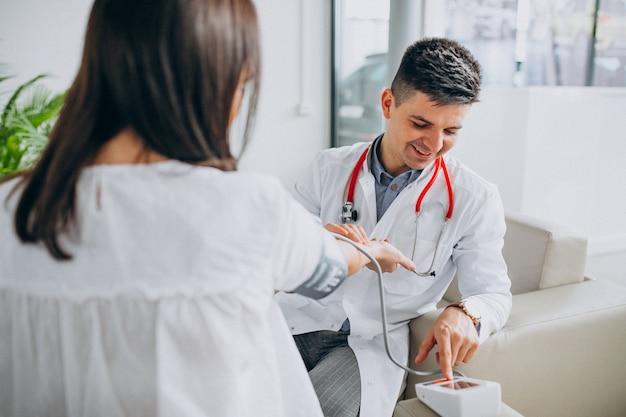 Joven médico masculino con paciente medir la presión sanguínea