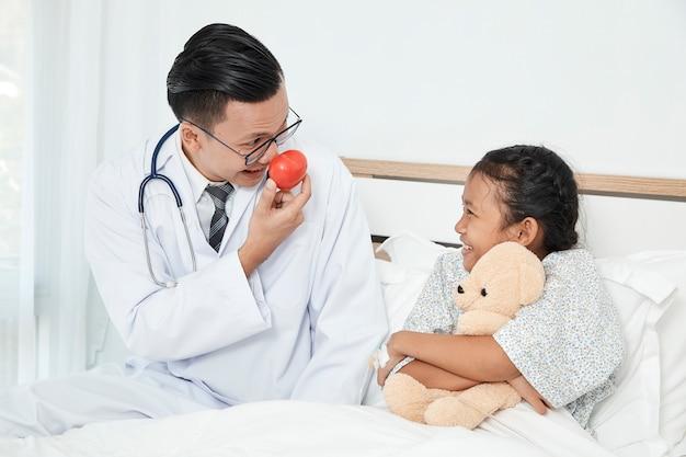 Joven médico masculino pediatra comprobación de niña