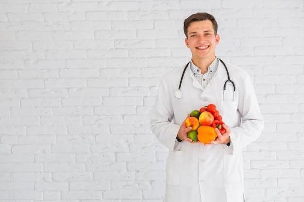 Joven médico masculino de pie contra la pared con alimentos saludables