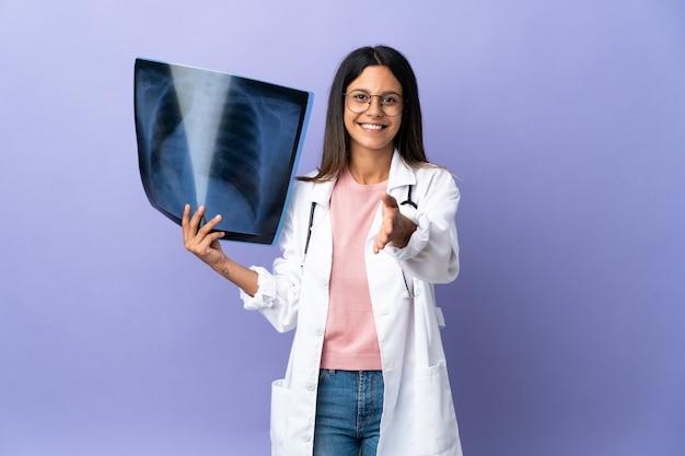 Joven médico mujer sosteniendo una radiografía dándose la mano para cerrar un buen trato