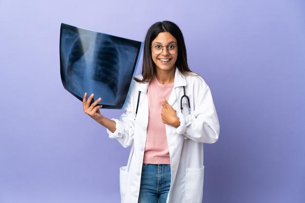 Joven médico mujer sosteniendo una radiografía con expresión facial sorpresa