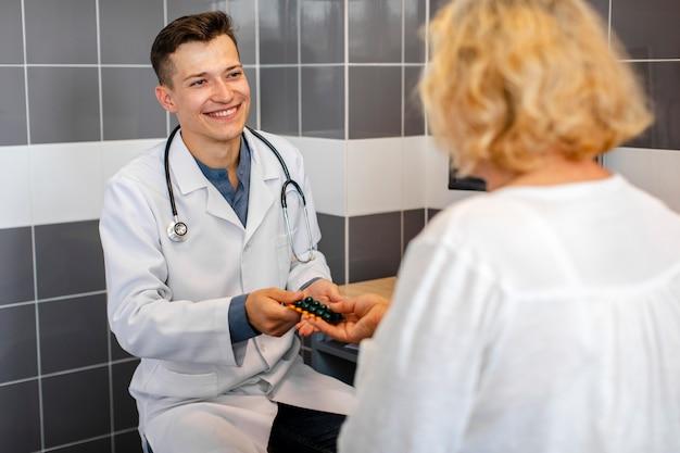 Joven médico ofreciendo píldoras a paciente femenino