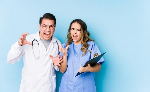Joven médico pareja posando en una pared azul aislado gritando de rabia.