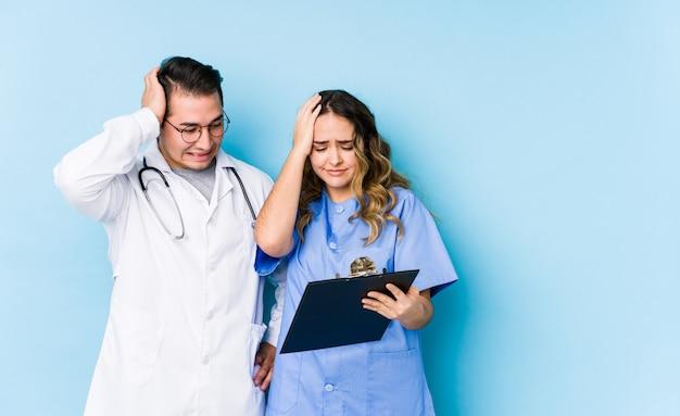 Joven médico pareja posando en una pared azul aislado olvidando algo, golpeando la frente con la palma y cerrando los ojos.