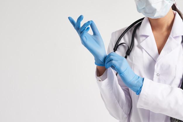Joven médico poniéndose guantes quirúrgicos