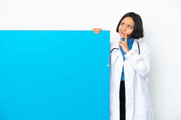 Joven médico de raza mixta mujer con un gran cartel aislado sobre fondo blanco con dudas mientras mira hacia arriba