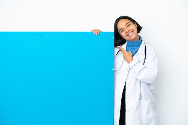 Joven médico de raza mixta mujer con un gran cartel aislado sonriendo y mostrando el signo de la victoria