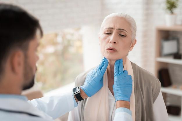 Joven médico revisa los ganglios linfáticos de una anciana.