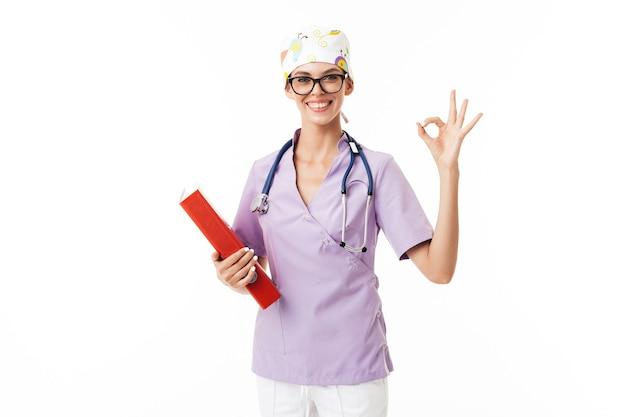 Joven médico sonriente en uniforme y anteojos con fonendoscopio en el cuello mostrando feliz gesto ok mientras