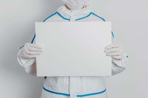 Joven médico sosteniendo un cartel en blanco
