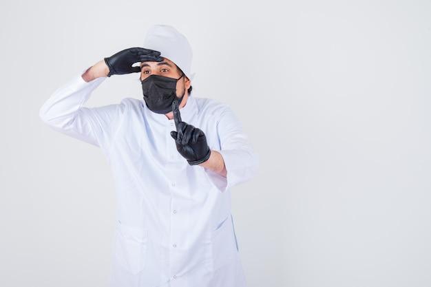 Joven médico sosteniendo la mano en la frente mientras muestra el número uno en uniforme blanco y mira enfocado, vista frontal.