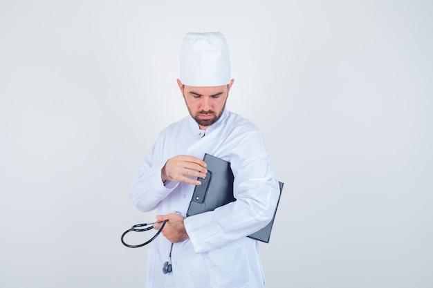 Joven médico sosteniendo el portapapeles y un estetoscopio en uniforme blanco y mirando pensativo, vista frontal.