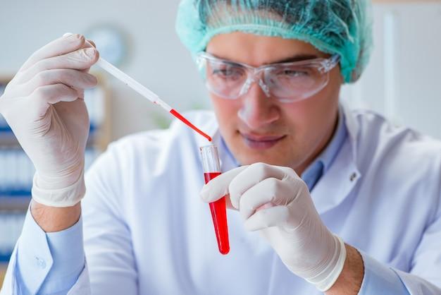 Joven médico trabajando en análisis de sangre en el hospital de laboratorio