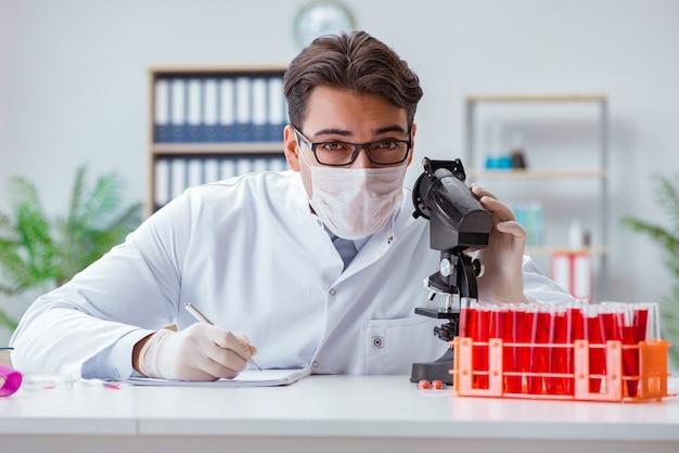Joven médico trabajando en el laboratorio con microscopio