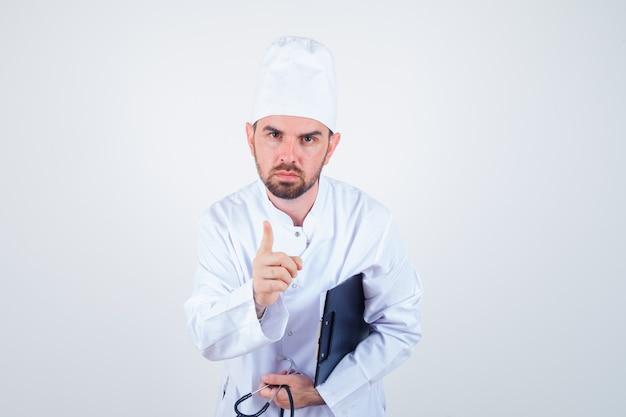Joven médico en uniforme blanco sosteniendo portapapeles, estetoscopio, advertencia con el dedo y mirando serio, vista frontal.