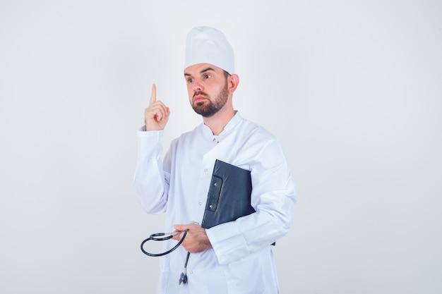 Joven médico en uniforme blanco sosteniendo portapapeles, estetoscopio, apuntando hacia arriba y mirando inteligente, vista frontal.
