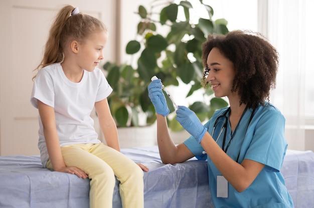 Joven médico vacunando a una niña