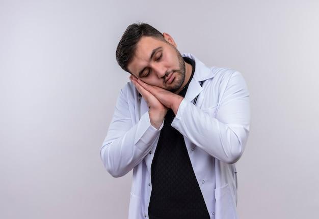 Joven médico varón barbudo con bata blanca con estetoscopio sosteniendo las palmas juntas inclinando la cabeza sobre las palmas quiere dormir