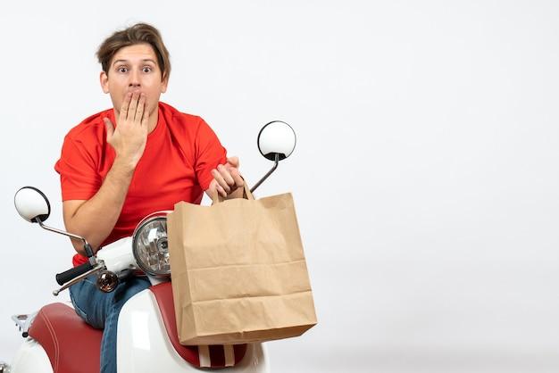 Joven mensajero desconcertado en uniforme rojo sentado en scooter sosteniendo una bolsa de papel en la pared amarilla