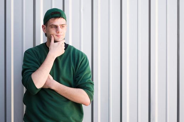 Joven mensajero con gorra verde tocando la barbilla
