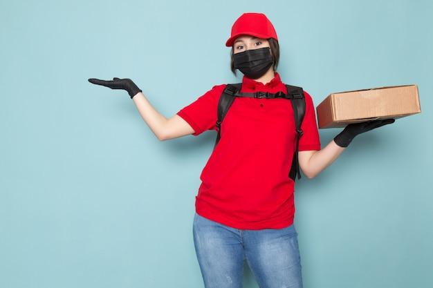 Joven mensajero en polo rojo gorra roja máscara protectora estéril negra mochila negra con paquete en azul