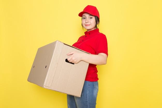 Joven mensajero en polo rojo gorra roja con paquete sonriendo en amarillo