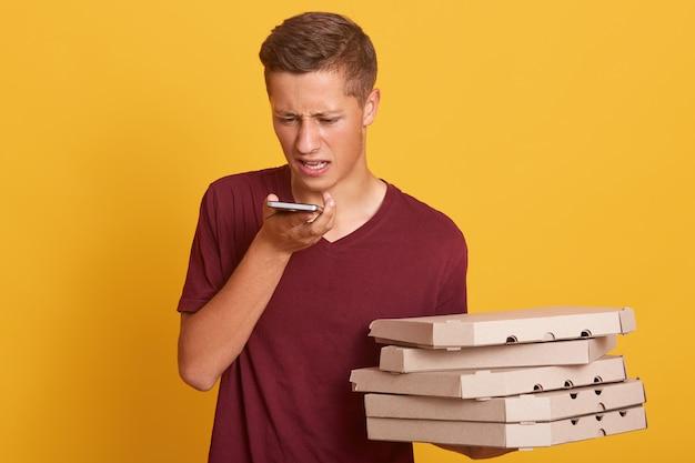 Joven mensajero que tiene una conversación desagradable con el cliente por teléfono, sosteniendo cajas con pizza